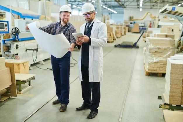 Wesoły inżynier przedstawiający projekt inwestorowi w białym fartuchu