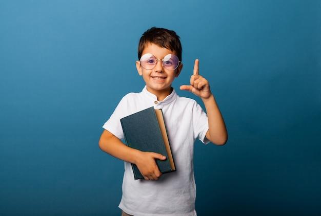 Wesoły, kaukaski chłopiec trzymający książkę w dłoniach. chłopiec z książką wskazuje palcem na niebieskim tle.