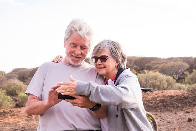 Wesoły kaukaski dorosły starszy para z rowerem górskim razem uprawiający zdrowy sport na świeżym powietrzu - starsi ludzie lubią starsze osoby jeżdżące na łonie natury i cieszące się stylem życia
