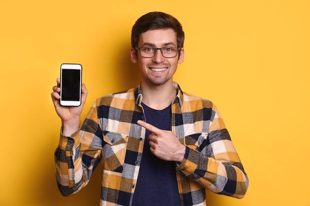 Wesoły kaukaski mężczyzna w okularach, wskazując palcem na pusty wyświetlacz smartfona w dłoni, uśmiechnięty, patrząc w kamerę, czat, porady, reklama. pojedynczo na żółto