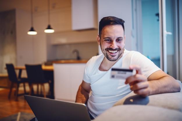 Wesoły kaukaski mężczyzna w piżamie siedzi w salonie na kanapie z laptopem na kolanach i kartą kredytową w ręku