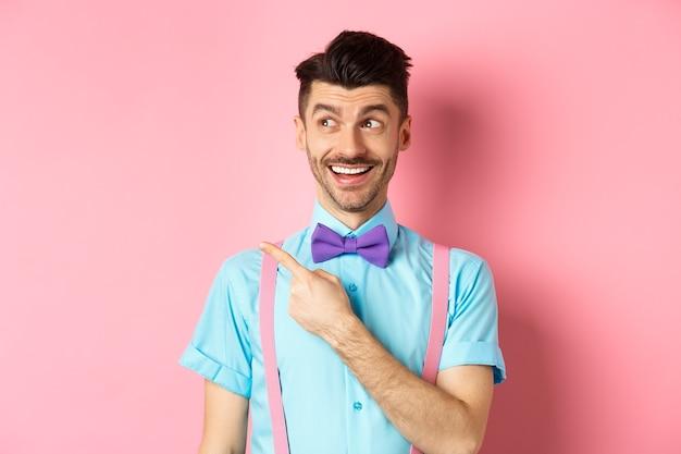 Wesoły kaukaski mężczyzna w śmiesznej muszce, patrząc i wskazując ręką w lewo, pokazując logo promocyjne, stojąc na różowym tle. skopiuj miejsce