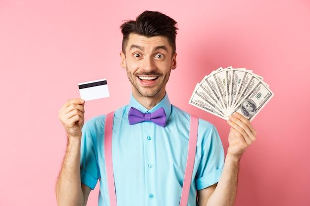 Wesoły kaukaski mężczyzna z wąsem i muszką pokazujący plastikową kartę kredytową z pieniędzmi w dolarach, uśmiechając się do kamery, stojąc nad różem.