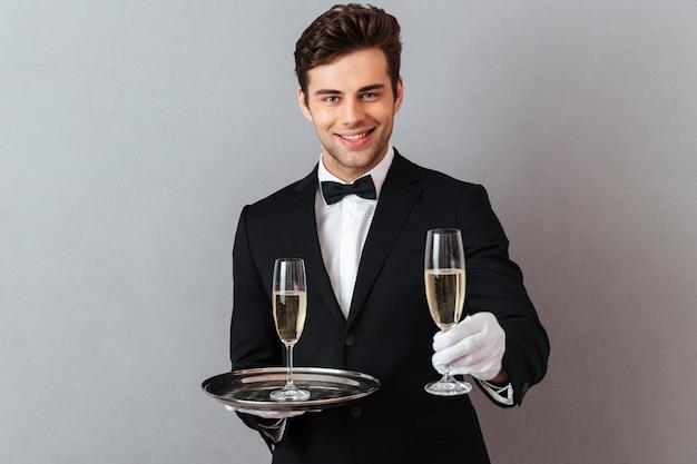 Wesoły kelner trzyma kieliszek szampana.