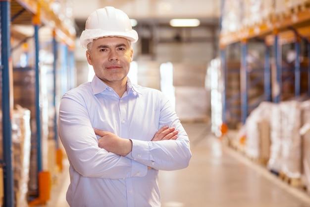 Wesoły kierownik logistyki, uśmiechając się, ciesząc się wykonywaniem swojej pracy