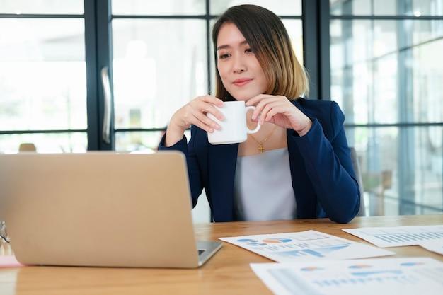 Wesoły kobieta trzymając filiżankę kawy w biurze i patrząc na kamery.