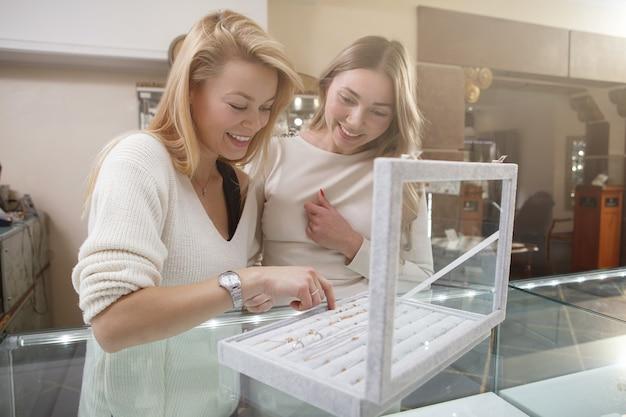 Wesoły koleżanki, ciesząc się razem zakupy biżuterii