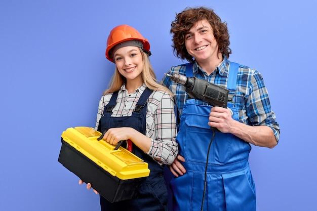 Wesoły konstruktorzy z narzędziami instrumentów pozowanie na białym tle na niebieskiej ścianie