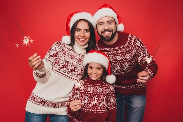 Wesoły krewni z błyszczącą małą kobietą w tradycyjnych strojach bożonarodzeniowych z dzianiny