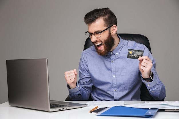 Wesoły krzyczący brodaty elegancki mężczyzna w okularach raduje się i trzyma kartę kredytową podczas korzystania z laptopa siedzącego przy stole w biurze