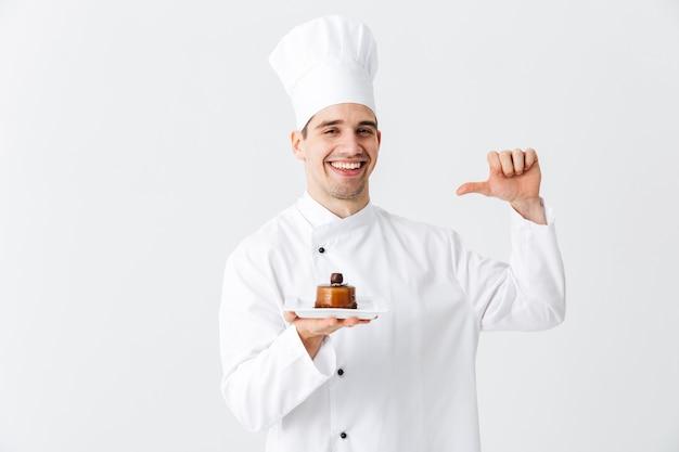 Wesoły kucharz człowiek ubrany w mundur pokazując ciasto na talerzu na białym tle nad białą ścianą