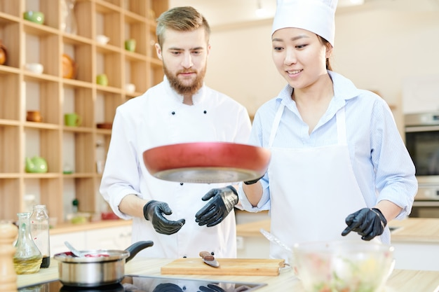 Wesoły kucharzy pracujących w kuchni