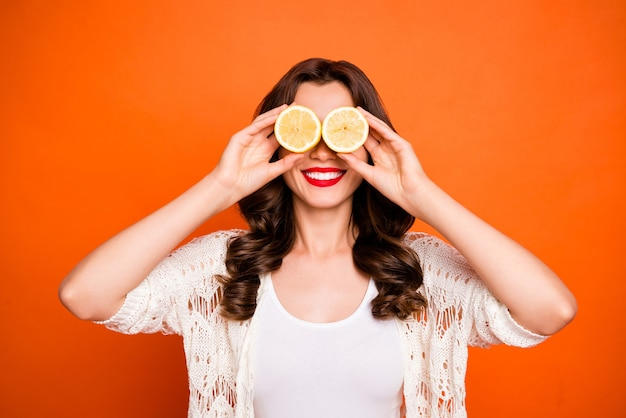 Wesoły ładny ładny uroczy urocza ładna kobieta patrząc na dwie połówki cytryn uśmiechnięty ząb promienieje.