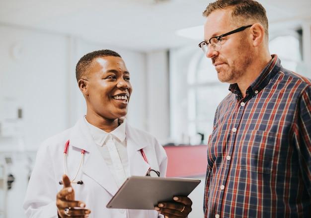 Wesoły lekarz daje pacjentowi dobre wieści