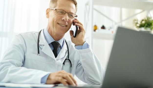 Wesoły lekarz rozmawia przez telefon komórkowy i korzysta z laptopa w klinice
