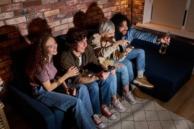 Wesoły ludzie grający w gry wideo, odpoczywający wieczorem w domu, organizujący rywalizację podczas gry, ubrani niedbale