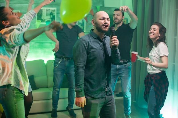 Wesoły łysy mężczyzna robi karaoke dla swoich przyjaciół na imprezie.