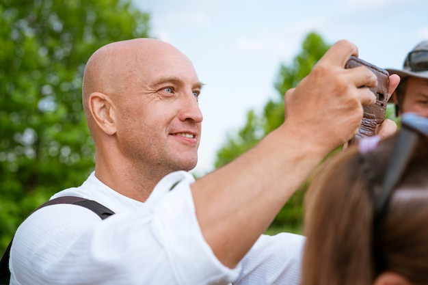 Wesoły łysy mężczyzna w białej koszuli robi zdjęcia telefonem w naturze