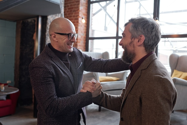 Wesoły łysy mężczyzna w okularach ściskający dłoń z przyjacielem, podekscytowany widokiem go we własnym domu