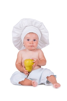 Wesoły małe dziecko z gruszką w dłoniach w garniturze szefa kuchni na białym.