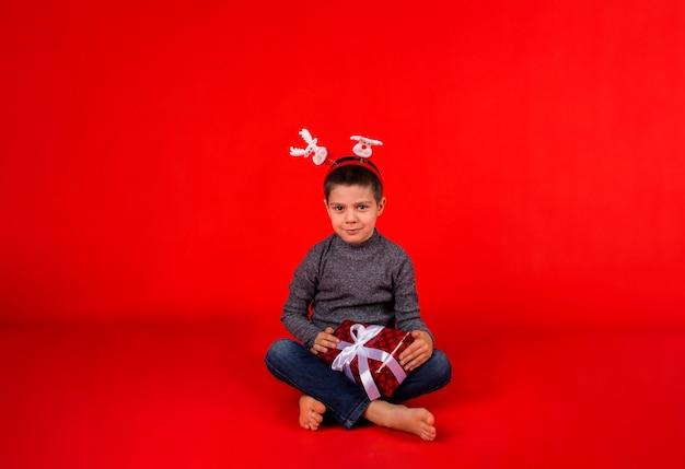 Wesoły maluch chłopiec w swetrze i świątecznej opasce z reniferem i prezentem siedzi na czerwono