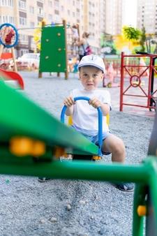 Wesoły mały chłopiec na huśtawce na placu zabaw