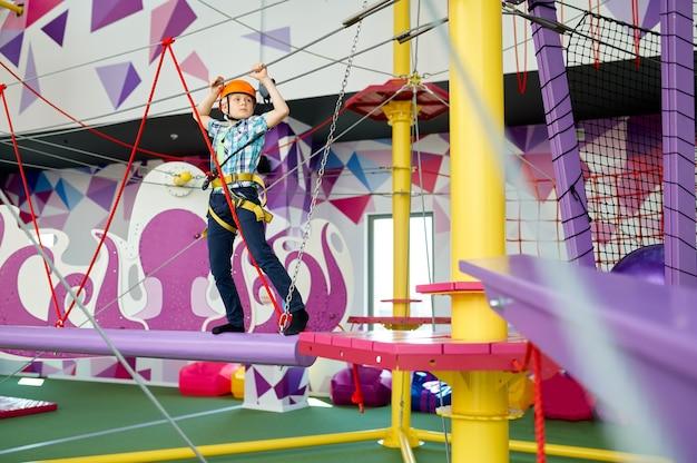 Wesoły mały chłopiec na linii zip w centrum rozrywki. dzieci bawiące się na terenie wspinaczkowym, dzieciaki spędzają weekend na placu zabaw, szczęśliwe dzieciństwo