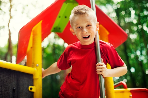 Wesoły mały chłopiec na placu zabaw
