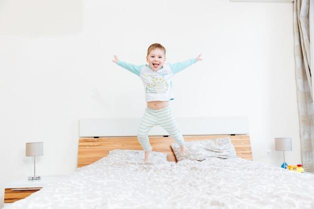 Wesoły mały chłopiec pokazujący język i skaczący na łóżku w domu