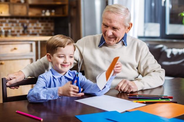 Wesoły mały chłopiec robi wycinanki podczas robienia świątecznej kartki ze swoim dziadkiem