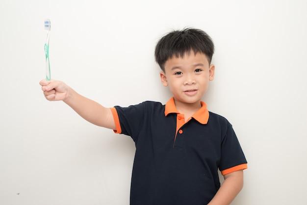 Wesoły mały chłopiec trzyma szczoteczkę do zębów na białym tle, studio portret zdrowego chłopca rasy mieszanej z szczoteczką do zębów na białym tle.