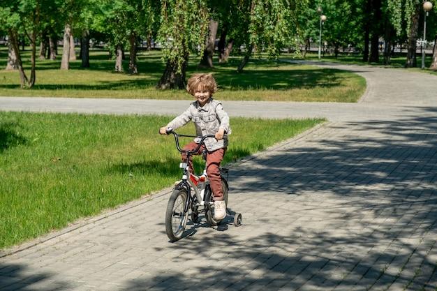 Wesoły mały chłopiec w codziennym stroju jeżdżącym na rowerze w słoneczny letni dzień, poruszając się po drodze wśród zielonych trawników i cieni drzew w parku