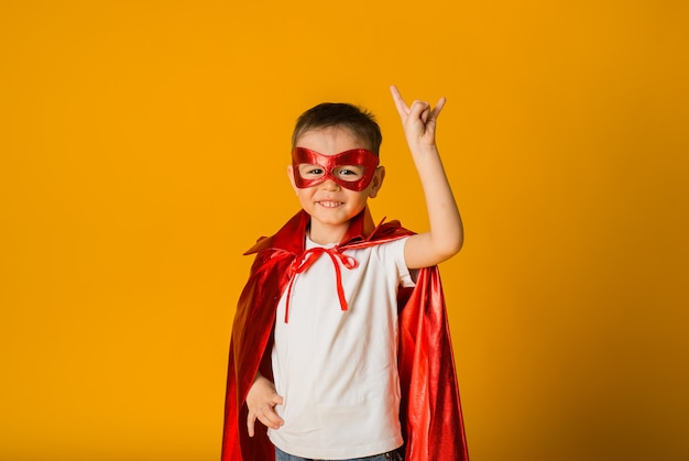 Wesoły mały chłopiec w stroju bohatera na żółtej powierzchni z miejscem na tekst