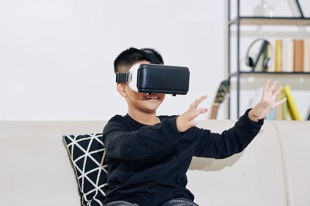 Wesoły mały dzieciak w zestawie słuchawkowym wirtualnej rzeczywistości gra w domu
