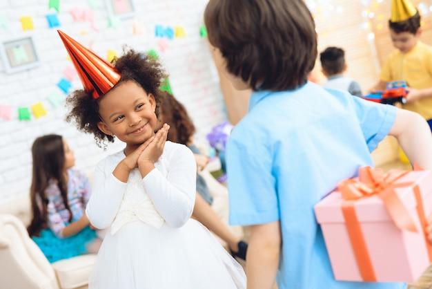Wesoły mały urodziny dziewczyna czeka na prezent.
