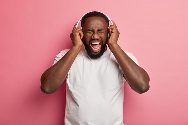 Wesoły meloman słucha ulubionej muzyki w słuchawkach, cieszy się dobrym dźwiękiem, ma otwarte usta i głośno krzyczy, nosi zwykłą białą koszulkę, pozuje w studio na różowej ścianie
