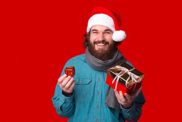 Wesoły męski hipster trzyma dwa prezenty na przyjęcie wigilijne.