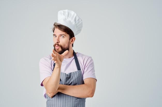 Wesoły męski szef kuchni w mundurze pracującym w profesjonalnej kuchni