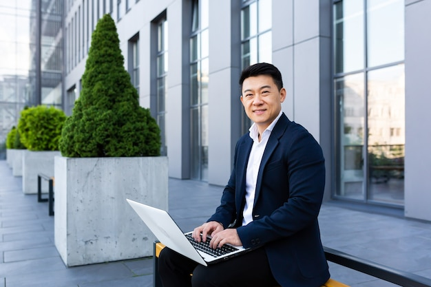 Wesoły mężczyzna azjatycki biznesmen pracujący na laptopie bankowości internetowej na komputerze w pobliżu centrum biurowego, patrząc na kamerę i uśmiechając się
