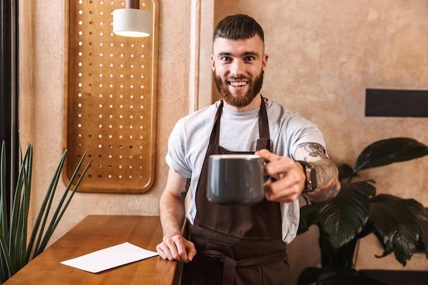Wesoły mężczyzna barista w fartuchu stojący w kawiarni, pokazując filiżankę kawy