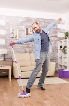Wesoły mężczyzna bawiący się myciem podłogi w mieszkaniu