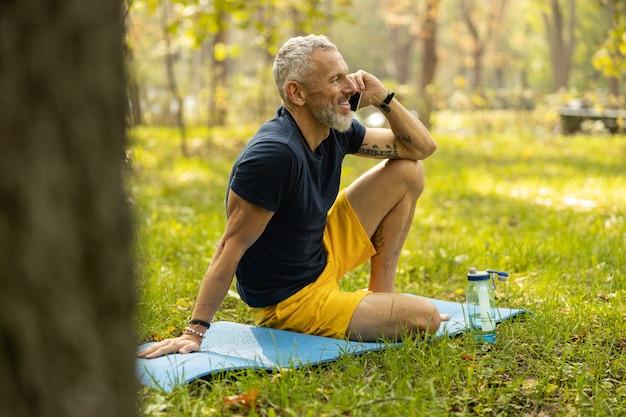 Wesoły mężczyzna dzwoniący podczas treningu w drewnie