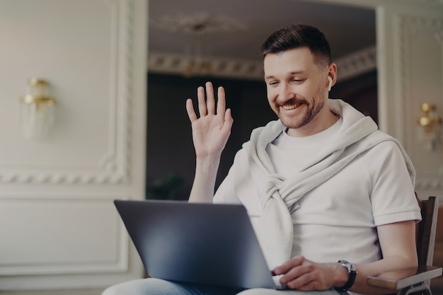 Wesoły mężczyzna freelancer w słuchawkach bezprzewodowych ubrany w zwykłe ubrania, machający do kogoś i uśmiechający się, siedząc przed komputerem, prowadząc rozmowę wideo z kolegami w nowoczesnym biurze domowym