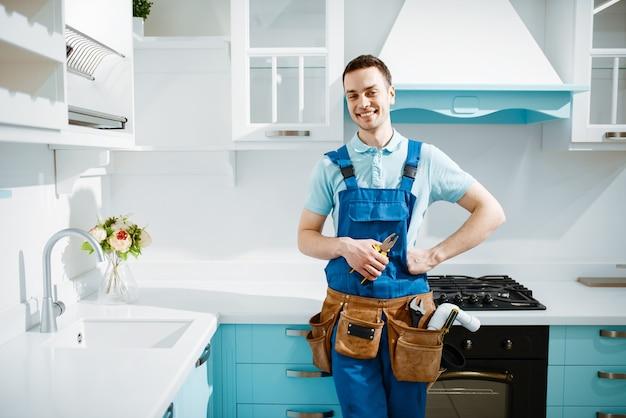 Wesoły mężczyzna hydraulik w jednolitych pozach w kuchni. złota rączka z zlewem do naprawy torby narzędziowej, serwis urządzeń sanitarnych w domu