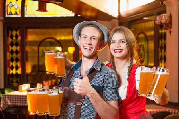 Wesoły mężczyzna i dziewczyna kelnerzy w strojach ludowych podczas uroczystości październik październik trzymają w rękach wiele kufli piwa.