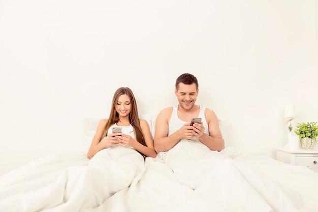 Wesoły mężczyzna i kobieta, leżąc w łóżku z telefonami i rozmawiając