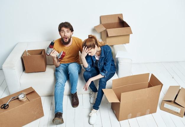 Wesoły mężczyzna i kobieta na kanapie przenosząc wewnętrzne kartony