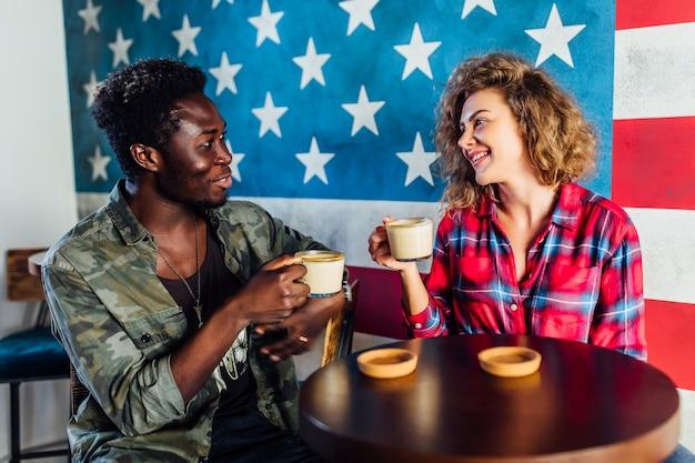 Wesoły mężczyzna i kobieta nastolatek najlepsi przyjaciele siedząc na tarasie kawiarni, picia kawy i mówienia.