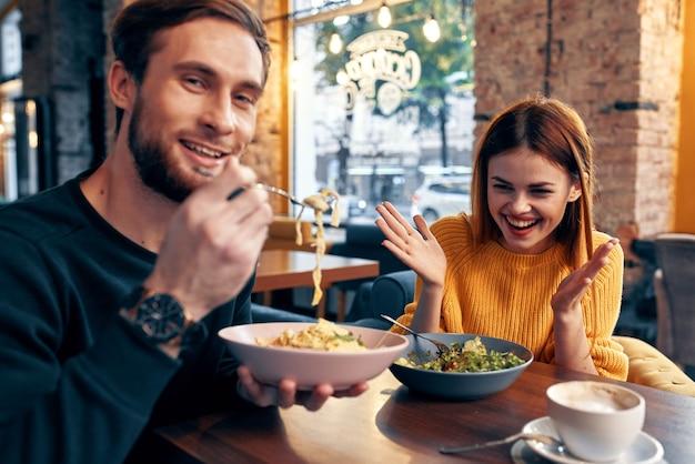 Wesoły mężczyzna i kobieta siedzi w kawiarni, przekazując emocje