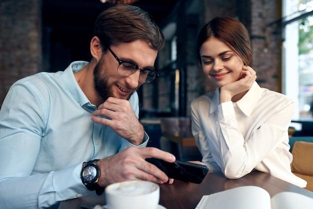 Wesoły mężczyzna i kobieta siedzi w kawiarni